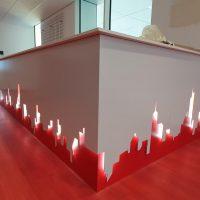 Svítící červeno-bílá dekorace na spodní části bílého pultu, obrysy panorama města, červená podlaha, bílé zdi