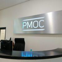 Stříbrná dibondová LED podsvícená deska obdélníkového tvaru na bílé stěně, svítící logo PMOC, v popředí recepční pultík
