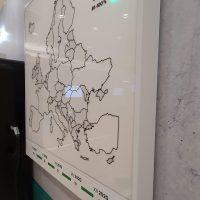 Bílá LED svítící dibondová deska s černou mapou Evropy a barevnými obdélníky, uchyceno na zdi
