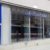 Z ulice vyfocená prodejna, vlevo vstupní brána s modrými okraji a modrým panelem nahoře, bílé nápisy, vpravo velká skleněná stěna, uprostřed stěny nahoře velký nápis COPY GENERAL, vpravo modrý panel s bílými nápisy, vpravo panelový dům