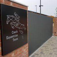 Černý LED prosvícený panel, s bílým logem Czech Equestrian Team, uchycen na cihlové zdi, šedá vrata