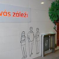 Bílá stěna v interiéru složená z velkých bílých obdélníků, nalevo bílý obdélníkový panel s oranžovo-červeným nápisem Na vás záleží, dole uprostřed černými obrysy znázorněné tři postavy - rodiče a dcera, vedle postav v popředí dva vstupní turnikety, vpravo namalovaný strom, v pozadí vpravo dva výtahy
