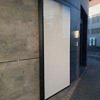 Bílý LED prosvícený panel s černým dibondovým rámem, uchycený na šedé zdi budovy