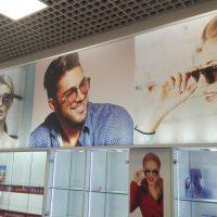 Prosvícená obdélníková LED deska potištěná fotografiemi lidí s brýlemi, svítící skleněné boxy, interiér optiky