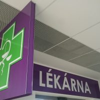 Fialová reklamní výstrč se znakem lékárny, zelený kříž, bílá obvodová linka, symbol váhy, Asklepiova hůl, dřevěné obložení