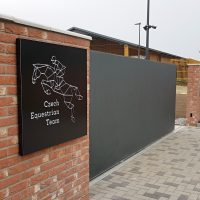 Černý světelný box s logem Czech Equestrian Team na cihlové zdi u vjezdu do areálu