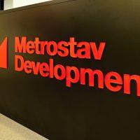 Červeně podlakované logo Metrostav Development z čirého plexiskla nalepené na černý recepční pult v místnosti se světlým kobercem a dveřmi v pozadí.