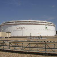 Značení naftové nádrže malovanou grafikou, celkový pohled, vepředu část oplocení, část administrativní budovy, obloha