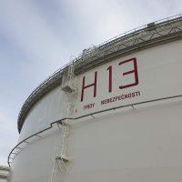 Malované logo H13 s informačním nápisem na naftové nádrži, detailní pohled zespoda, obloha