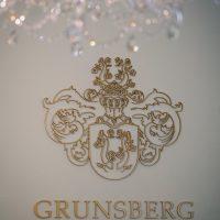 Laserem vyřezané dekorativní logo a nápis Grunsberg Jewellery z plexiskla lakovaného do zlaté barvy přilepené přímo na bílou zeď v místnosti se skleněným dekorativním lustrem.