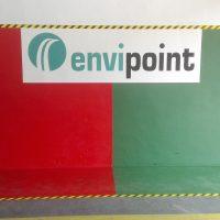 Malovaná grafika na zdi a podlaze garáže, červeno-zelené pole s logem envipoint