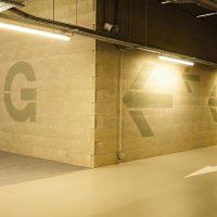 Malovaný navigační systém uvnitř garáže, nápis 1G na zdi, šipky na zdi za rohem, část značení EXIT na podlaze