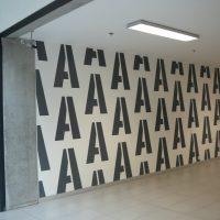 Černá písmena A několikrát se opakující, malovaná na bílé zdi, béžové dlaždice, stropní osvětlení, část skleněné příčky