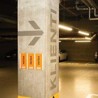 Detail značení sloupu uvnitř podzemní garáže, malovaná šipka a nápis KLIENTI, tabulky s označením pater připevněné ke sloupu, v pozadí parkovací místa s auty