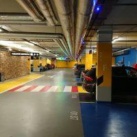 Značení uvnitř podzemní garáže, malovaná grafika na zdi a podlaze, piktogram handicapované osoby a označení čísly, navigační výstrče na stropě, zaparkovaná auta