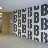 Černá písmena B několikrát se opakující, malovaná grafika na bílé zdi jako označení chodby, béžová podlaha, skleněno-dřevěné dveře