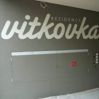 Bílý malovaný nápis REZIDENCE VITKOVKA na šedé zdi