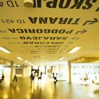 Názvy světových měst malované na stropě s orientačním značením, v pozadí rozostření lidé