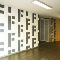 Malovaná grafika na zdi s opakovaným motivem stříbrného písmena F, chodba budovy ČSOB, dřevěná podlaha, stropní osvětlení, v pozadí vchodové dveře