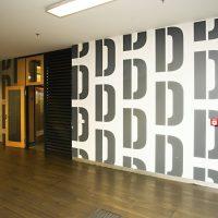 Šedé písmeno D několikrát se opakující na bílé zdi jako značení chodby, malovaná grafika, dřevěná podlaha, stropní osvětlení, otevřené dveře