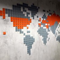 Šedooranžová 3D mapa světa zhotovená z malých čtverečků z podlakovaného plexiskla, vyřezávaných laserem a přímo přilepených na mramorovou/žíhanou šedobílou stěnu v interiéru.