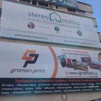 Kus panelové budovy pokrytý dvěma velkými reklamními bannery, vlevo prosklené čtverce, vpravo další šedo-bílá budova a strom