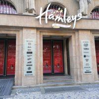 Vstup do budovy Hamleys, tři vchody, prosklené dveře s červenou grafikou, dvě informační cedule z mléčného skla na sloupech