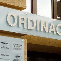 V detailu vyfocený mléčně bílý informační panel nad vchodem do budovy s velkým šedým nápisem, vlevo další mléčný panel s černými nápisy a logy