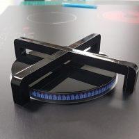 Plastový model sporákového hořáku s malými modrými plamínky po obvodu, na podkladu umělého sporáku