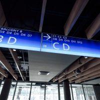 Dva modré podsvícené navigační panely s bílými nápisy, šipkami a symboly toalet, zavěšené ze stropu v prostoru haly, v pozadí velká prosklená okna a dva nosné sloupy
