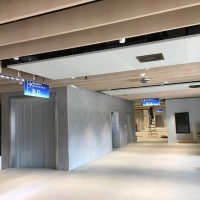 Stavební práce v interiéru O2 universum, montáž stropních výstrčí, LED podsvícení, muž na štaflích, betonové stěrky