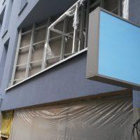 Panelové domy vyfocené zboku, na domě šedo-modré fasády v popředí připevněny tři modré reklamní výstrče s šedým lemováním, v pozadí další domy