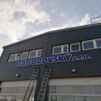 Tmavě šedá budova s mírné zkosenou střechou, v horní části okna s bílými obrysy, pod nimi veliký modrý nápis BABOROVSKÝ s.r.o. s bílým lemováním, pod nápisem dva stříbrné žebříky vedoucí dolů, v dolní části dvě garážová vrata bílé barvy