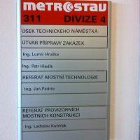 Modulový informační systém METROSTAV divize 4, označení útvarů, kovová tabulka přišroubovaná na bílé zdi