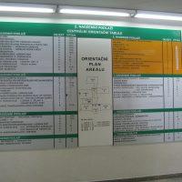 Modulový systém s orientačním plánem areálu a značením částí budovy, přimontováno na bílé zdi