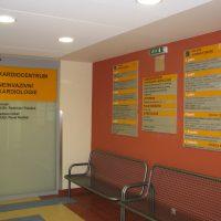 Modulový orientační systém přimontovaný na oranžové zdi chodby Kardiocentra, tři tabule se samolepicí plotrovou folií