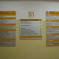 Tři tabule na zdi, modulový orientační systém zdravotnického zařízení, bílá tabulka s oranžovým značením S1