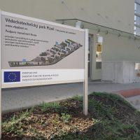 Stříbrný hliníkový stojan s barevným schématem budov Vědeckotechnického parku Plzeň a nabídkou podpory inovačních firem
