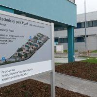 Stříbrný hliníkový stojan s barevným schématem budov Vědeckotechnického parku Plzeň, v pozadí řada kancelářských budov