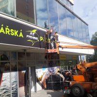 Technik na vysokozdvižné plošině instaluje desku s logem nad vchod prodejny rybářských potřeb, potištěné bannery na zdi budovy