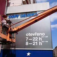 Technik na vysokozdvižném vozíku, samolepicí modré logo COPY GENERAL na budově, bílý nápis s otevírací dobouy