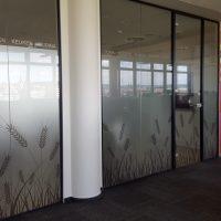 Pískovaná folie nalepená na skleněné příčce na chodbě, na spodní části vyřezané tvarby obilí, vedle fototapeta na stěně s motivem Johna Lennona