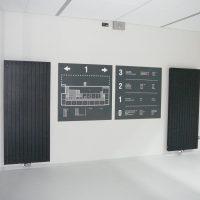 Dvě šedé čtvercové navigační tabule, bílé označení pater 0–3, orientační plán 1. podlaží, přimontováno na bílé zdi mezi šedými designovými radiátory