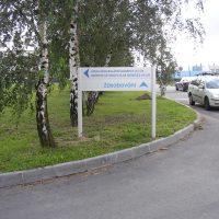 Šedá hliníková navigační cedule v travnaté ploše pod stromořadím bříz modré šipky a text, vlevo k ÚMG AV ČR, rovně zásobování