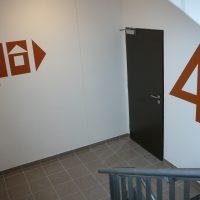Červená malovaná grafika na zdi, navigační piktogramy s šipkou a číslice 4 jako označení patra na chodbě budovy, černé dveře, část zábradlí, hnědé dlaždice na podlaze