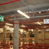 Dvě závěsné navigační tabulky s piktogramy, označení nouzového východu a směru k toaletám, zavěšené řetízky na stropě industriálního interiéru