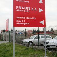 Červená cedule na šedých nohách, bílé navigační šipky a nápisy, betonové patky v trávě, dvě stříbrná auta za drátěným plotem