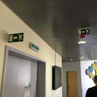 Dvě nesvětelné navigační výstrče s piktogramy únikového východu a šipkou, světelné značení EXIT nad dveřmi, dekorace ze šestiúhelníků na stěně, detail muže zezadu