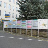 Řada stříbrných hliníkových stojanů tvořící orientační systém pavilonů nemocnice, žluté dopravní značení na asfaltu, zákaz parkování