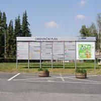 Šedý orientační systém s nápisem ORIENTAČNÍ PLÁN a znakem ÚVN, popis pavilonů nemocnice, dopravní značení zákaz parkování
